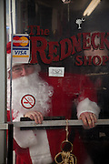 Santa Claus looks out from inside the Redneck Shop December 5, 2009 in Laurens, SC during the 7th Annual White Unity Christmas Party held by the American Nazi Party & International Knights of the Ku Klux Klan.