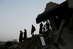 Palestinians climb down the rubble from their destroyed home in Jabaliya in the Gaza Strip.