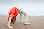 "Young girl being a ""crab"" on a beach, Scotland"