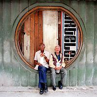 Elderly Cuban men sit in a boarded-up window of an old cinema in Havana, Cuba.