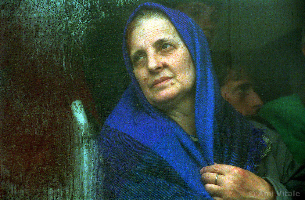 An ethnic Albanian refugee from Kosovo sits in a bus waiting to be transported to the Brazda camp near Skopje, Macedonia, Thursday, April 22, 1999.   (Photo By Ami Vitale)