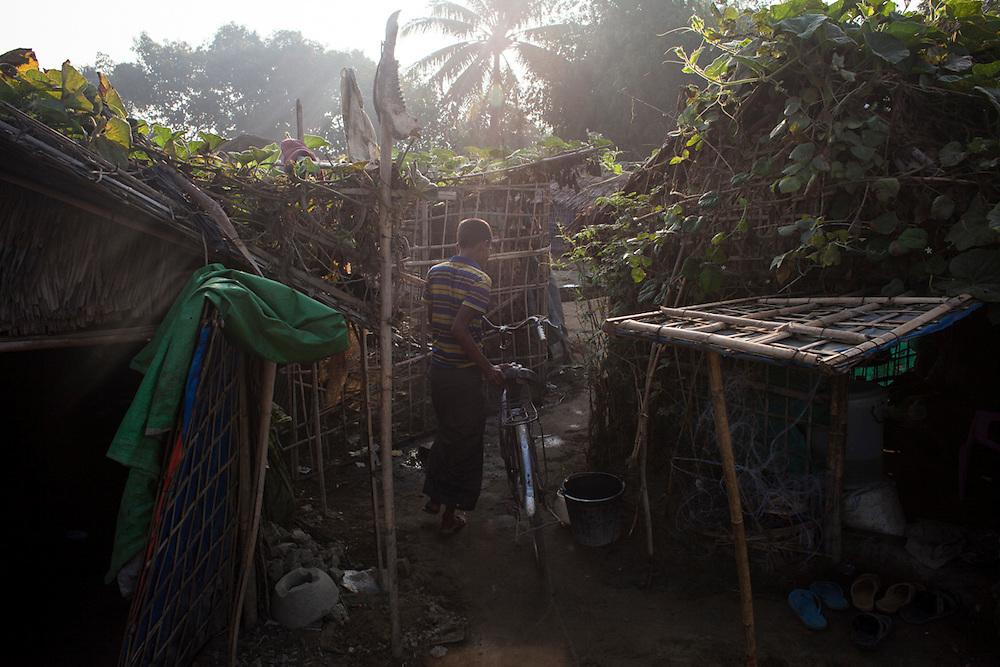 A boy walks his bike in an IDP camp in Sittwe, Myanmar.