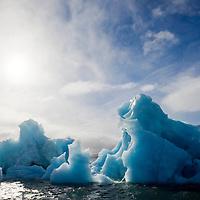 Norway, Svalbard, Nordaustlandet, Deep blue iceberg floating in Palanderbukta Bay along Gustav Adolf Land on stormy morning