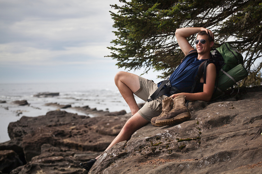 Henry Pedersen relaxes on the rocky shoreline at Dare Beach, West Coast Trail, British Columbia, Canada.