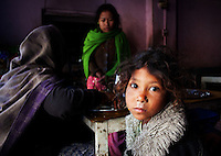 Poor girl and her family eating in a dirty cafe in Kathmandu, Nepal
