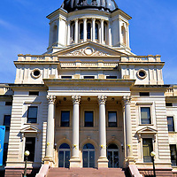 South Dakota State Capitol Building in Pierre, South Dakota<br /> South Dakota was inhabited by the Sioux Indians plus French and European settlers before the Lewis and Clark exploration in 1804. It then became part of the Dakota Territory in 1861 and the 40th state on November 2, 1889. 21 years later, the state capitol was finished in Pierre. It closely resembles Montana&rsquo;s capitol with a granite and limestone base, Corinthian columns and a copper dome.