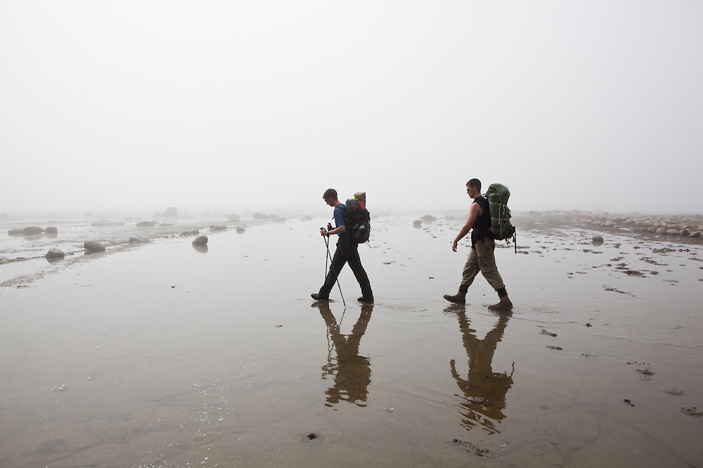 Zach Podell-Eberhardt (left) and Henry hike through shallow water on the continental shelf in the mist near Bonilla Point, West Coast Trail, British Columbia, Canada.