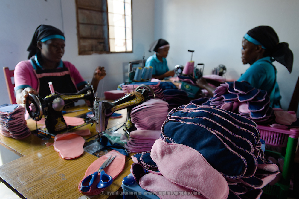 Annette Namale (left), Bridget Nakuya and Josephine Namukasa sewing sanitary pads at the Afripads factory in the village of Kitengeesa in the Central Region of Uganda on 30 July 2014.<br /> <br /> Started by volunteers in 2009, Afripads manufactures reusable fibre sanitary pads made locally by community residents. Beginning with a single employee, the company now employs roughly 100 women and produces approximately 700 kits (consisting of pads, holders and a bag) each week. At USh 12,000 to 15,0000 (&pound;2.75 to &pound;3.40) for a kit that lasts approximately one year, Afripads offer a significant saving over disposables which may cost in excess of USh 42,000 (&pound;9.60) over the course of a year. And for the many girls and women who cannot afford disposables, they offer an affordable and more hygienic alternative to rags, cotton wool or toilet paper, all of which are frequently used. At schools where Afripads have been distributed, teachers report that absenteeism has dropped sharply as girls who previously did not have access to proper sanitary pads now no longer stay home when they have their periods.