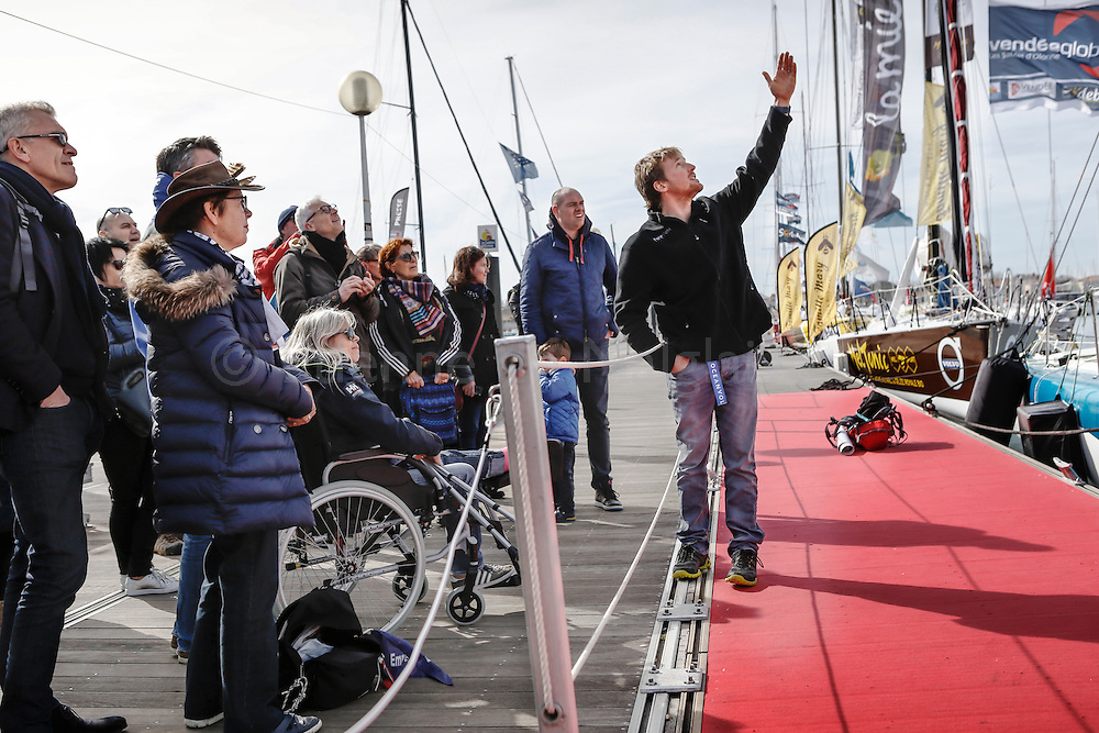 New Zealand sailor Conrad Colman on his boat the day after he crossed the Vendee Globe Race finish line in Sables d'Olonne. Describing to onlookers the jury rig mast he built at sea. 25 February 2017.