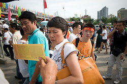 People try to buy tickets from scalpers outside the National Staium  during the Beijing 2008 Olympic Games August 23, 2008. (Photo By Ami Vitale)