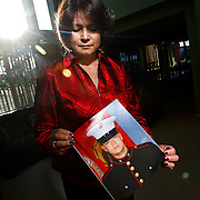 "SHOT 6/11/08 6:51:01 PM - Veronica DeLuccie, 48, of Brighton, Co. poses with a portrait of her 20 year-old son Matthew Shane Armendariz at their home in Brighton on Wednesday June 11, 2008. Armendariz is  a Marine stationed in Fallujah, Iraq and has a wife and 18 month-old son back in Colorado. DeLuccie said she had hoped he wouldn't enlist but supports him nonetheless and said, ""every day I pretend I don't know where he's at"". She added that it was his life long dream to serve in the military and he sees it as a way to provide for his family..(Photo by Marc Piscotty / WpN)"