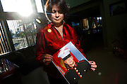 """SHOT 6/11/08 6:51:01 PM - Veronica DeLuccie, 48, of Brighton, Co. poses with a portrait of her 20 year-old son Matthew Shane Armendariz at their home in Brighton on Wednesday June 11, 2008. Armendariz is  a Marine stationed in Fallujah, Iraq and has a wife and 18 month-old son back in Colorado. DeLuccie said she had hoped he wouldn't enlist but supports him nonetheless and said, """"every day I pretend I don't know where he's at"""". She added that it was his life long dream to serve in the military and he sees it as a way to provide for his family..(Photo by Marc Piscotty / WpN)"""