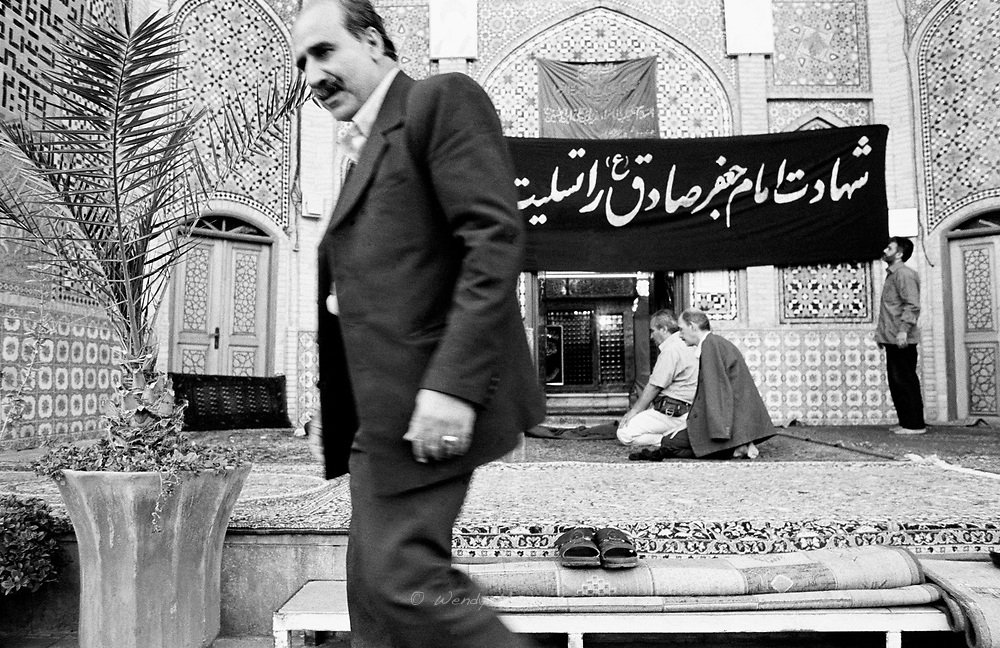 A man leaving, while other men are still praying, at the mausoleum of the son of the third Imam. Tehran, Iran, 2007