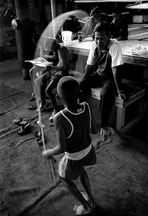 11 year old Tao is watched by his father at the Muay Thai Boxing Club under the freeway at Khlong Toei, Bangkok Thailand March 2003.©David Dare Parker / AsiaWorks Photography