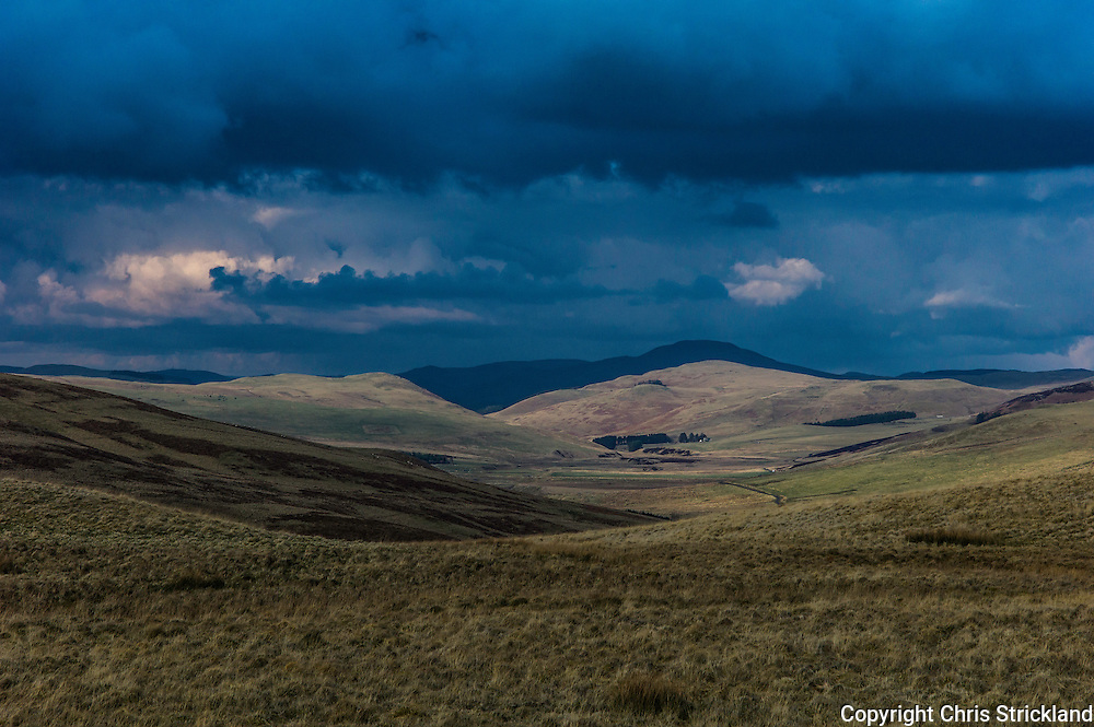 Hownam, Kelso, Scottish Borders, UK. 27th February 2016. Storm clouds gather over the Cheviot Hills which straddle the Anglo Scot Border as the late afternoon sun illuminates the Kale Valley.
