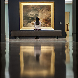 London, UK - 8 September 2014: a gallery assistant looks up at 'A disaster at sea, 1835' <br />  by J.M.W. Turner, during the press preview of The EY Exhibition: Late Turner &ndash; Painting Set Free exhibition at Tate Britain