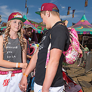 Teen couple in matching pants and hats, at the midway at the Clallam County Fair.