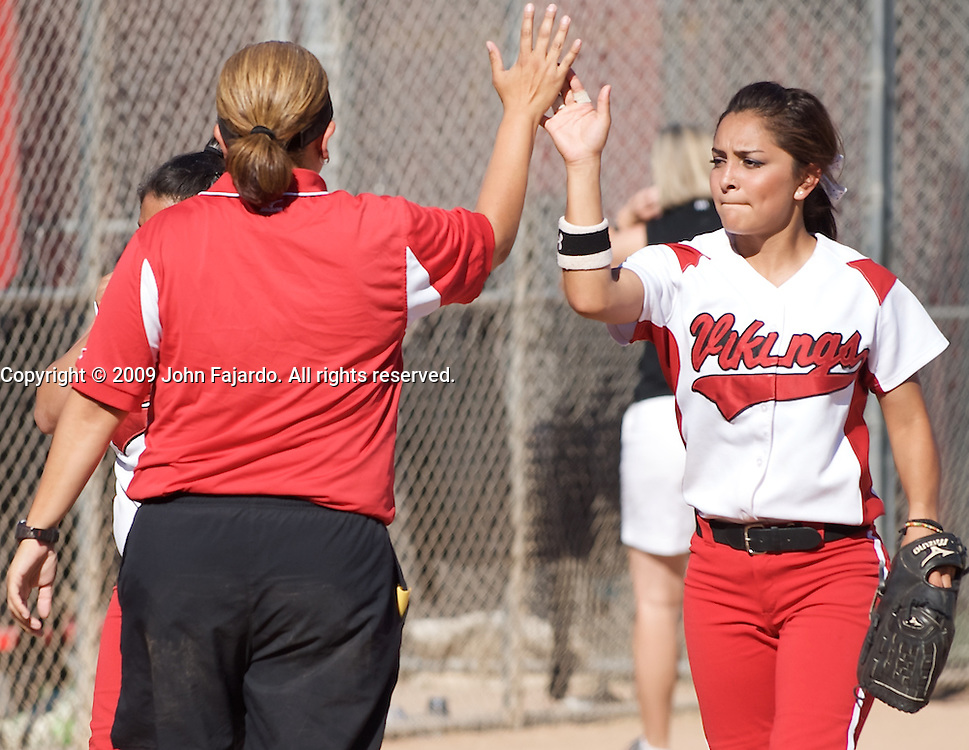 LBCC's Karina Martinez and Coach Melissa Angel high five after retiring the side in the game against Mt. SAC at the LAC softball field on Tuesday April 21, 2009.  The Vikings lose the final regular season home game 5-1.