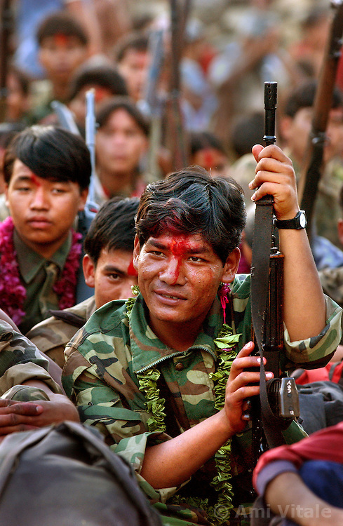 """RUKUM DISTRICT, NEPAL, APRIL 22, 2004:  Maoist insurgents celebrate in Rukum district April 22, 2004 weeks after their attack on government troops in Beni when they overran the district headquarters, looting a bank, destroying the jail and torching government office buildings. The government said that 32 security personnel died in the clash and 37 were kidnapped. The clash was one of the deadliest since 1996 when fighting began to topple the constitutional monarchy and install a communist republic. The guerrillas' strength is hard to gauge. Analysts and diplomats estimate there about 15,000-20,000 hard-core fighters, including many women, backed by 50,000 """"militia"""".  In their remote strongholds, they collect taxes and have set up civil administrations, and """"people's courts"""" to settle rows. They also raise money by taxing villagers and foreign trekkers. Though young, they are fearsome fighters and  specialise in night attacks and hit-and-run raids. They are tough in Nepal's rugged terrain, full of thick forests and deep ravines and the 150,000 government soldiers are not enough to combat this growing movement that models itself after the Shining Path of Peru. (Ami Vitale/Getty Images)"""