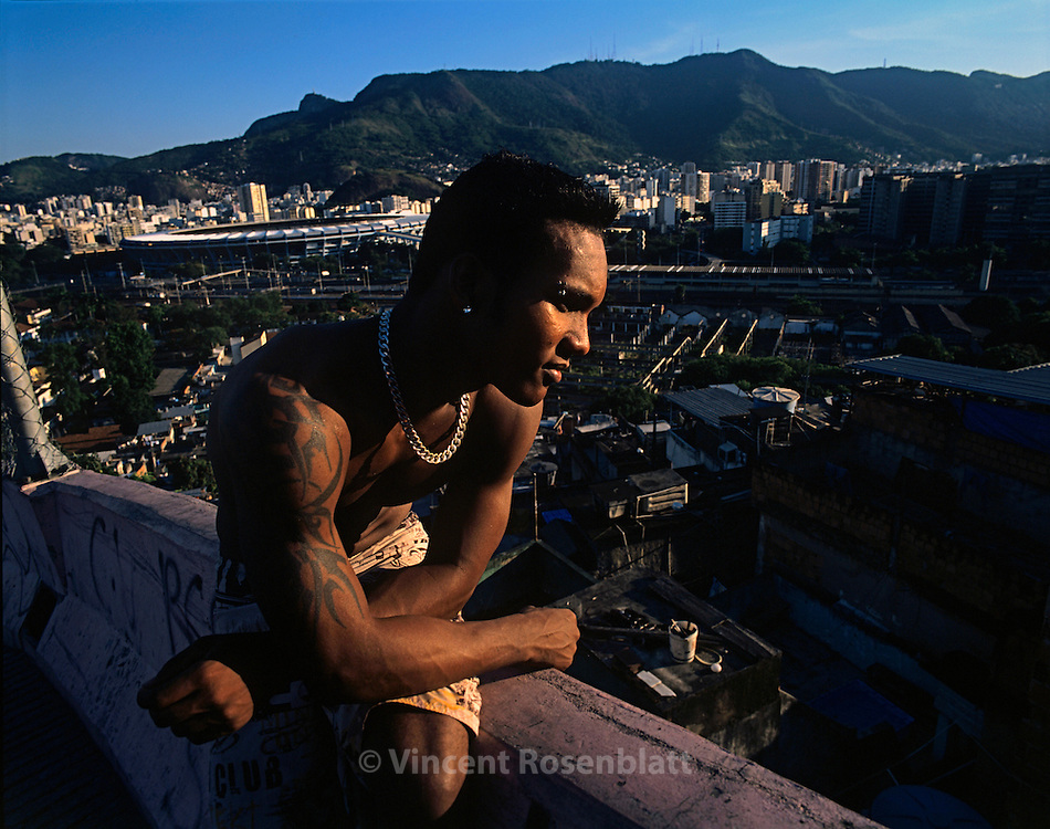 """Mangueira favela, Rio de Janeiro.  Diego, leader of the boys band """"Muleks 100 limits"""" (""""boys without limits"""") looks at Mangueira slum, from the heights of the hill, dreaming that his group """"Muleks 100 limits"""" will have success on the carioca funk scene.  In the background on the left, one can see the mythical Maracana stadium."""