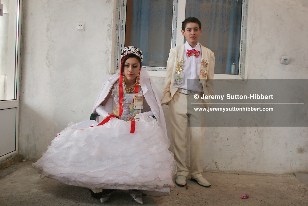 Garoafa Mihai, aged 14 (on left), and Florin 'Ciprian' Lulu, aged 13 (on right), Roma (gypsies) on their wedding day in the village of Sintesti,15 kilometres from Bucharest, Romania, on Saturday, Sept 23rd 2006. Their partnership was decided by their parents and not through love, and under Romanian law is illegal. The children will neither complete legal paperwork for the wedding, nor visit the local Romanian Orthodox church for a blessing. On her wedding day Garoafa wore approximately 30-40,000 USD of gold Franz Josef coins on her dress, part of the large dowry that she takes with her as she begins her married life. For the guests and for the people of the village another 30,000 USD of pigs were killed to be eaten and given away as presents of food. Another 30,000 USD was spent on famous Roma musicians to come and sing 'manele'  type music at the wedding extolling the wealth and status of their patrons for the weekend in their songs.