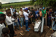 EL SEIBO, DOMINICAN REPUBLIC - OCTOBER 13, 2013: Family members and friends mourn during the burial of a young woman born in the Dominican Republic, to Haitian parents, at a cemetery in an impoverished batey next to sugar cane fileds in El Seibo.  The woman was affected by judgment TC/0168, handed down by the Constitutional Court of the Dominican Republic.  The ruling essentially revokes Dominican citizenship from tens of thousands of people born in the Dominican Republic, which means they cannot have access to government services, id's necessary for legal work and travel, and the children cannot attend public school.  NGO workers said the day before she died, the woman had  been trying to get a birth certificate for her baby, which as denied.  The woman said he was very upset for not being able to register her baby, despite that it had been born in the Dominican Republic. Family members could not afford to pay for an autopsy, nor to prepare her body for burial, so they buried her the same day that she died.  Because of the judgement, family members could not get a death certificate. CREDIT: Meridith Kohut for The New York Times