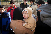 An 8 month old baby cries whilst waiting to be processed at the police headquarters in Mytilene, Lesvos.  Image © Angelos Giotopoulos/Falcon Photo Agency..