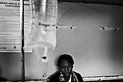 A woman waiting for treatment at the admissions and screening section of a Cholera Treatment Centre in Harare. the sign in the background on Shona language gives advice on the prevention of Cholera...Children and adults are treated at Beatrice Road Infectious Diseases Clinic in Harare, Zimbabwe...The clinic is staffed by locals but assisted by MSF.