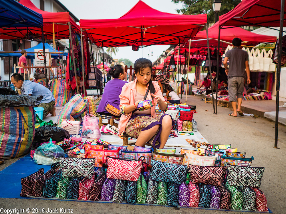 """11 MARCH 2016 - LUANG PRABANG, LAOS:  A vendor sets up her souvenir stand in the handicraft market in Luang Prabang. Luang Prabang was named a UNESCO World Heritage Site in 1995. The move saved the city's colonial architecture but the explosion of mass tourism has taken a toll on the city's soul. According to one recent study, a small plot of land that sold for $8,000 three years ago now goes for $120,000. Many longtime residents are selling their homes and moving to small developments around the city. The old homes are then converted to guesthouses, restaurants and spas. The city is famous for the morning """"tak bat,"""" or monks' morning alms rounds. Every morning hundreds of Buddhist monks come out before dawn and walk in a silent procession through the city accepting alms from residents. Now, most of the people presenting alms to the monks are tourists, since so many Lao people have moved outside of the city center. About 50,000 people are thought to live in the Luang Prabang area, the city received more than 530,000 tourists in 2014.      PHOTO BY JACK KURTZ"""