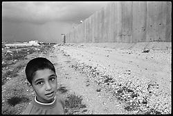 A Palestinian boy walks near Israel's war in Qalqilya, occupied West Bank.
