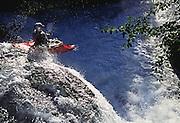 A kayaker negotiates a waterfall while running Davis Creek on Alaska's Seward Penninsula.