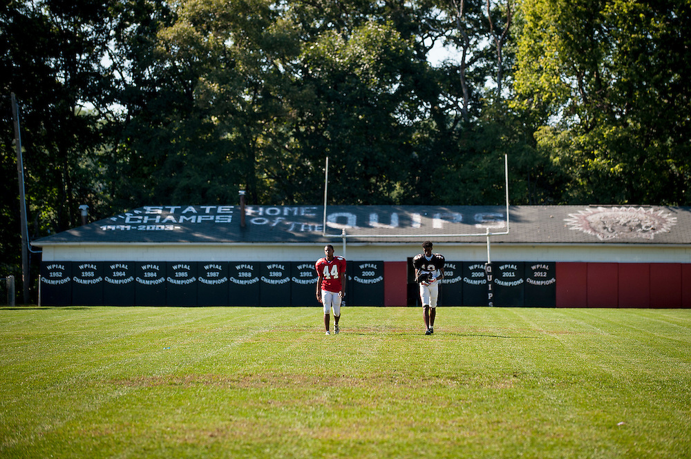 Players on the Aliquippa High School football team walks across Carl A. Aschman Stadium on their way to the practice field to prepare for their homecoming game.<br /> <br /> The school has one of the smallest enrollments in the Western Pennsylvania Interscholastic Athletic League (WPIAL) with the class of 2013 having only 58 kids, including 28 boys.<br /> <br /> Technically, they could play against Class A completion but they elect to play at the AA level.<br /> <br /> Pretty steep obstacles for a coach and team to overcome, but the team averaged 10 wins a year for the past 30 years. Last year Aliquippa played in its 25th WPIAL championship game, the most of any school in the district and they have won a record 15 titles. 2014 was the seventh year in a row that the Quips were in the final, also a record.