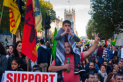 London, October 11th 2014. Thousands of protesters from the UK's Kurdish community demonstrate in London against the delay in assisting the people of the Syrian city of Kobane in their fight against ISIS. They also accuse Turkey, with whom the Kurds have had a long-running insurgency of siding with the Islamic State by doing nothing to help Kurds in Kobane. PICTURED: A boy shouts slogans from his vantage point on a man's shoulders.