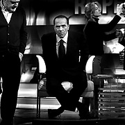 """Italian Prime Minister Silvio Berlusconi adjustes his microphone before taking part at the  in a politic talk show at the italian """"RAI"""" broadcast studios .The italian politics leader made his first TV appereance after 8 months, to draw a balance of his five years government and to welcome the resignation of Bank of Italy Governor Antonio Fazio."""