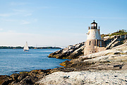 The iconic Castle Hill Lighthouse greets sailboats in the late summer sun at the entrance to Newport Harbor in historic Newport, Rhode Island.