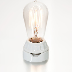 Vintage illuminated light bulb in a ceramic socket