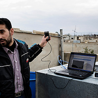 SYRIA - Al Qsair. A Syrian reporter is seen on a roof as he is tryng to get cellphone network to file videos, in Al Qsair, on January 28,  2012. Al Qsair is a small town of 40000 inhabitants, located 25Km south-west of Homs. The town is besieged since the beginning of November and so far it counts 65 dead.In all Syria there are hundreds of non-professional reporters who without experience and without proper gear keep documenting, day after day, the crackdown of the regime. This series of pictures is dedicated to them... to this colleagues who among every kind of difficulties and risks let know to the word their stories and drama.  ALESSIO ROMENZI