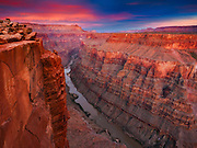 The pink light of sunset brings an ethereal glow to the cliffs of Toroweap, 3,000 feet above the Colorado River. Grand Canyon National Park, Arizona.