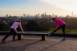 December 11th 2014. Two women do stretching exercises against the backdrop of London's skyline
