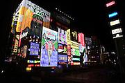 Nenreclames schreeuwen om de aandacht van de mensen in het uitgaansgebied van Osaka