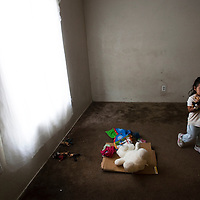 Apartment complex where migrant workers live is dilapadated and infested. This family can't sleep in this room because of the extensive water damage and rot. Several of the girls toys lay on the cardboard.