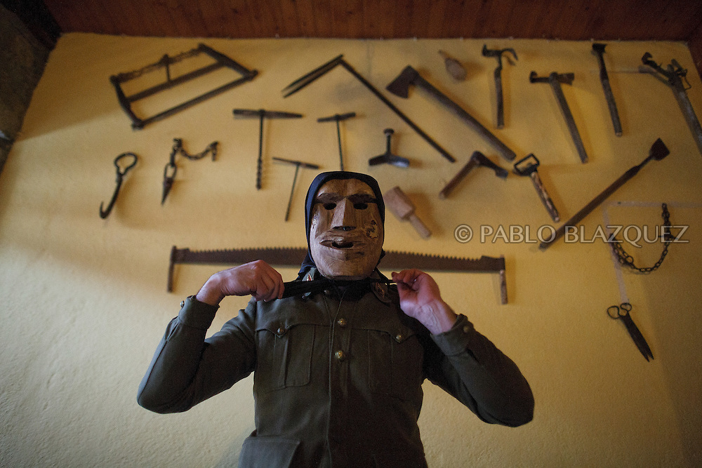 A Machurrero from Pedro Bernardo puts on a mask and black handkerchief before walking the streets during carnival on February 6, 2016 in Pedro Bernardo, in Avila province, Spain. The origins of this pagan festival are unknown. The Machurreros wear wood masks, a military dress, black handkerchief, cowbells, and hold wicker stick. The festival disappeared after Dictator Franco forbid carnival festivals in 1937, but it was recently recovered. Before disappearing, male villagers after the military service, used to dress as Machurreros as they run along the streets scaring children and adults with their wicker stick to bring fertility to the land and expel the evil spirits. (© Pablo Blazquez)