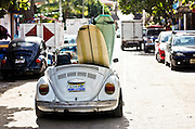 """SHOT 1/15/10 11:15:41 AM - A pair of surfboards hang out the back end of a topless Volkswagen Beetle on the streets of Sayulita, Mexico. Sayulita is a small fishing village about 25 miles north of downtown Puerto Vallarta in the state of Nayarit, Mexico, with a population of approximately 4,000. Known for its consistent river mouth surf break, roving surfers """"discovered"""" Sayulita in the late 60's with the construction of Mexican Highway 200. In recent years, it has become increasingly popular as a holiday and vacation destination, especially with surfing enthusiasts and American and Canadian tourists. (Photo by Marc Piscotty / © 2009)"""