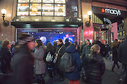 tourists walking in front of Macy's in New York City during Christmas time