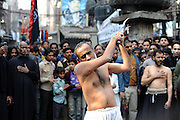 A man is hitting himself with ceremonial knives during Ashura. Ashura commemorates a day of mourning for the death of Hussein ibn Ali, the grandson of the Prophet Muhammad, at the battle of Karbala.  Shias consider Hussein the third Imam and the rightful successor to Muhammad. The grief for his death is demonstrated by the self-flagellation.  Lahore, Pakistan, 2009