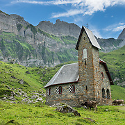 """At Meglisalp, Altmann peak (2435m on right) rises dramatically above a 1904 mountain chapel (Kapelle Maria zum Schnee, """"Holy Mother Mary of the Snow""""). Berggasthaus Meglisalp can only be reached on foot in the heart of the Alpstein mountain chain in the Appenzell Alps, Switzerland, Europe. This authentic mountain hostelry, owned by the same family for five generations, dates from 1897. Meglisalp is a working family dairy farm."""