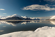 Ice breaks up the reflection of the Kenai Mountains in Turnagain Arm at high tide in Southcentral Alaska. Winter. Afternoon.