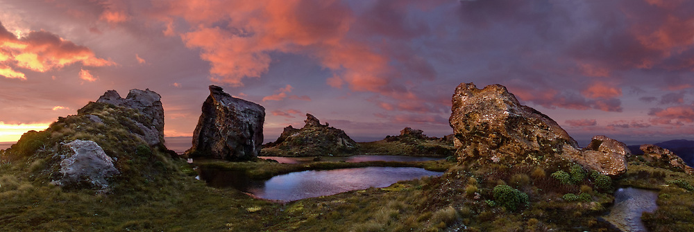 """Sunrise illuminates the curious tors and tarns (crags and ponds) on Hump Ridge, a track (trail) for trampers (hikers and trekkers) in Fiordland National Park, South Island, New Zealand. In 1990, UNESCO honored Te Wahipounamu - South West New Zealand as a World Heritage Area. Published in """"Light Travel: Photography on the Go"""" book by Tom Dempsey 2009, 2010. Panorama stitched from 5 overlapping images."""