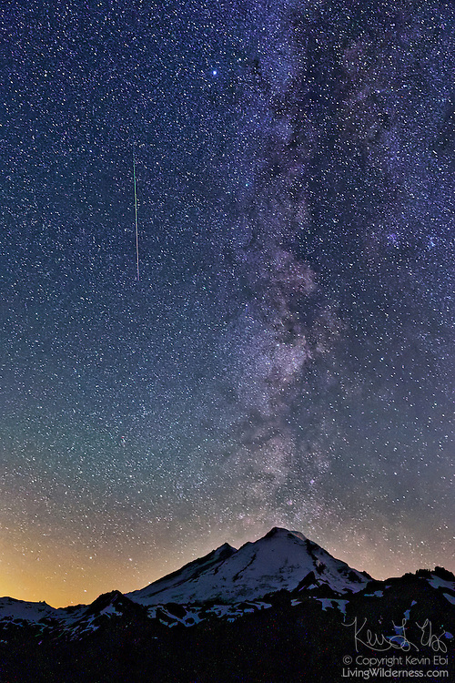 A meteor from the Perseid meteor shower streaks along the Milky Way, which appears to erupt from Mount Baker in Washington state. The Perseids are an annual meteor shower that occurs in August when Earth passes through the debris of Comet 109P/Swift-Tuttle. The meteors are comet debris burning up in the Earth's atmosphere. Mount Baker, which stands 10,781 feet (3,286 meters), is an active volcano with the second-most thermally active crater in the Cascade Range.