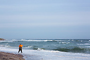 large fisherman surfcasting in the Winter long the Montauk coastline